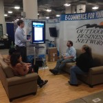 Trade show booth with salesperson presenting software to clients on couches.